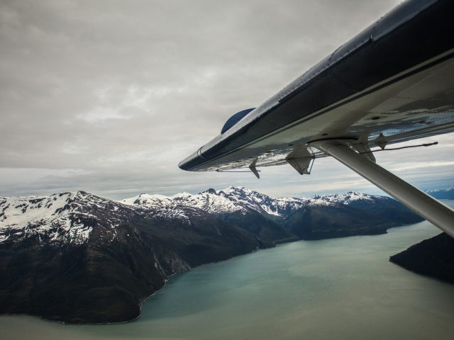Plane wing over Alaskan fjord