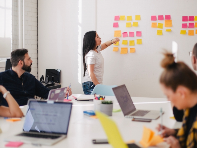 Woman using sticky notes on a white board, group watches