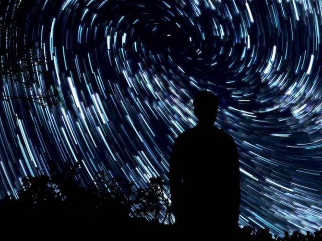 silhouette of a person in front of night sky full of stars - credit jeremy thomas, unsplash