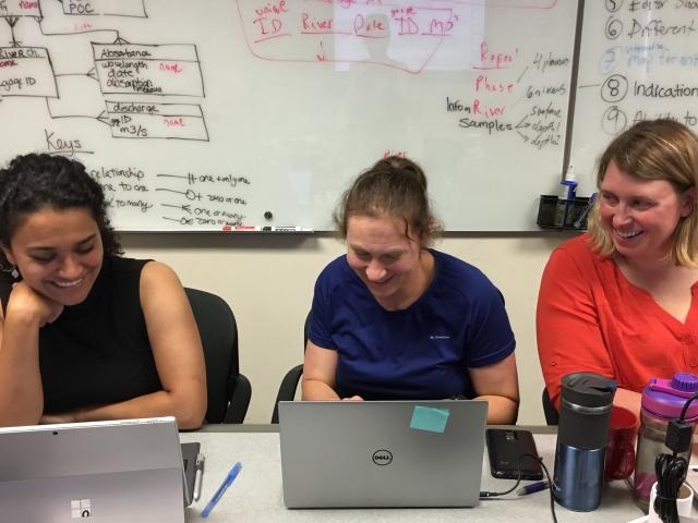Three women sitting at laptops smiling