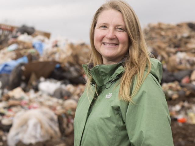 Jenna Jambeck standing in front of trash heap
