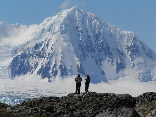 Two people standing in front of snowy mountain