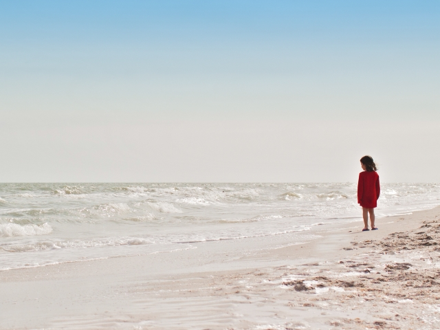 Young girl in red dress standing on beach
