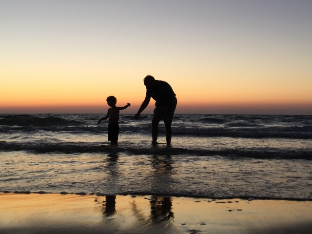 Man and boy playing in ocean at sunset
