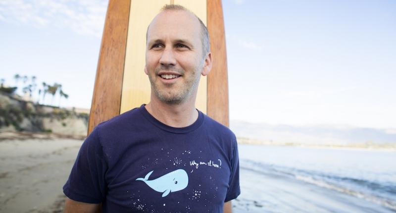 Ben Halpern standing with surf board on beach