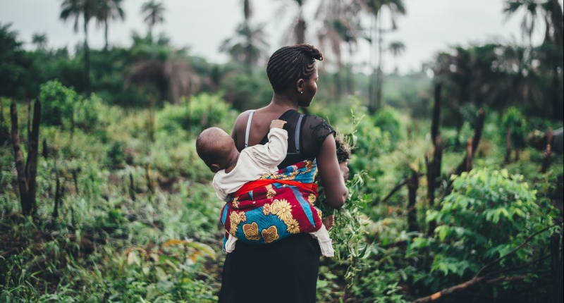 Mother carries child on back in tropical forest