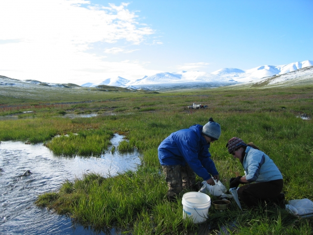 Two female researchers taking samples and mountains in background